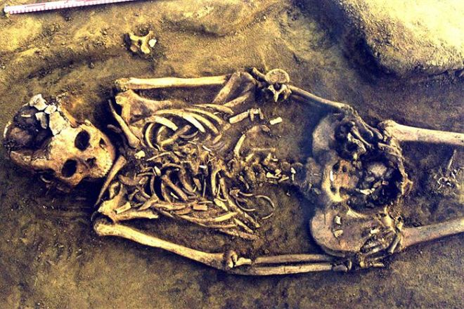 Image: The skeleton of prehistoric mother in her grave. The small bones in her pelvic-abdominal area and between her thighs are the remains of twins. Credit: Angela Lieverse.
